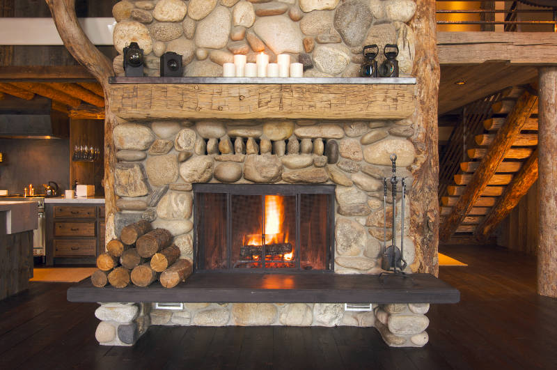a wood mantle on a stone fireplace