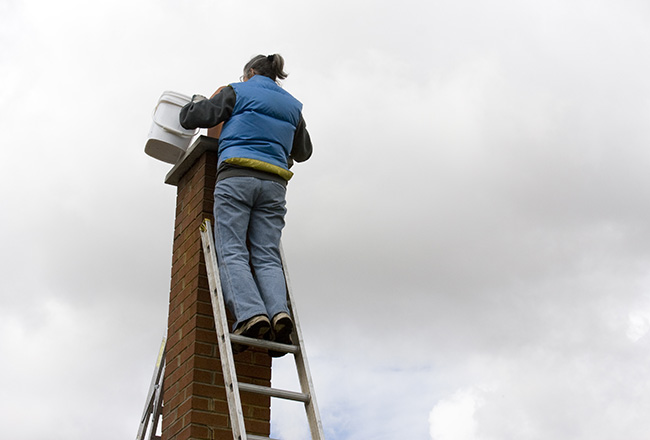 professional woman is waterproofing a brick chimney