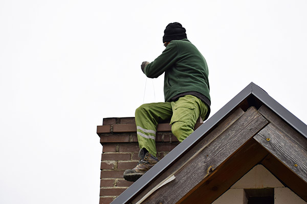 Man performing a chimney inspection.