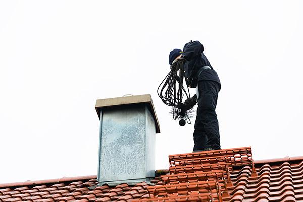Expert doing chimney inspection